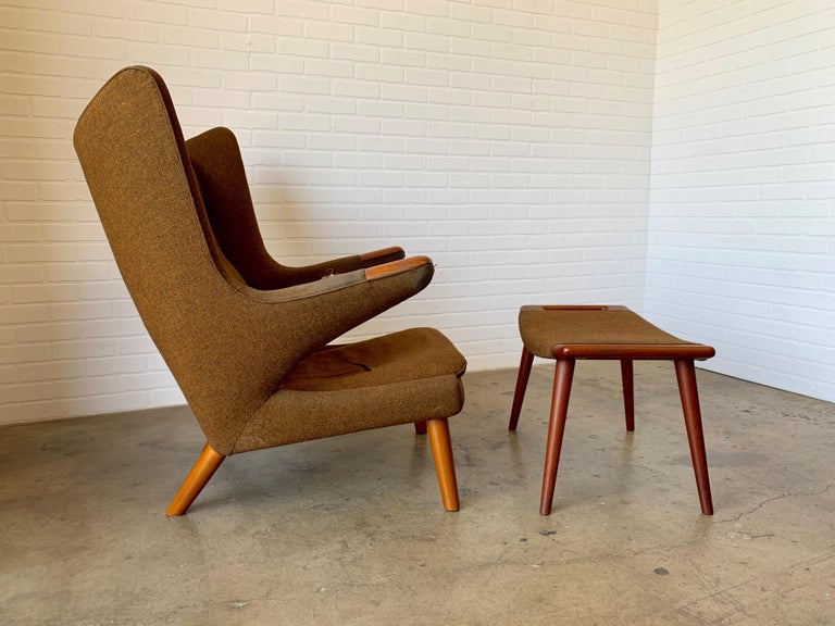 Danish modern papa bear chair and ottoman by Hans Wegner. Manufactured by A.P. Stolen. This piece is all original condition; the wood and frame are sound but needs new upholstery Retains the original stamp to the bottom. Original Danish control tag