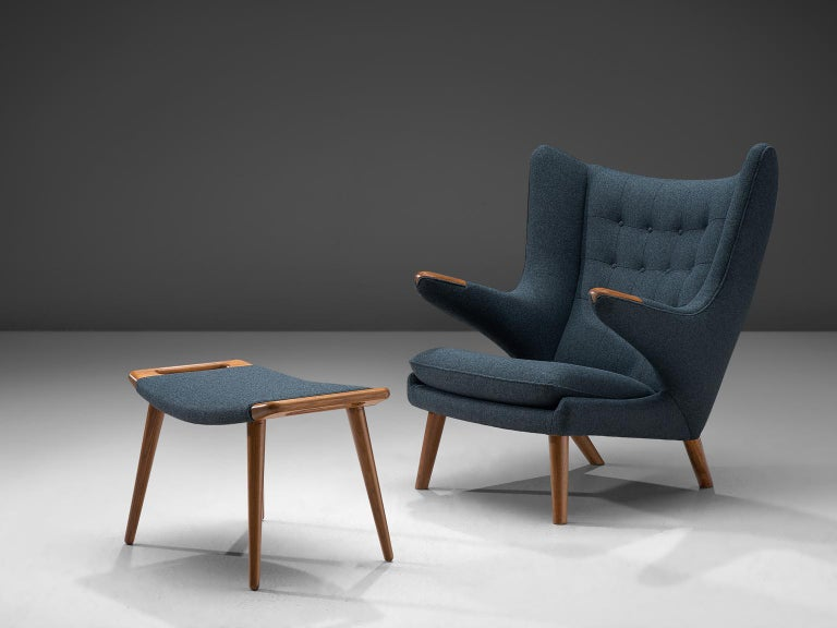 Hans J. Wegner by AP Stolen, lounge chair Model AP 19 'Papa Bear with footstool, Denmark, 1951 design, production late 1950s, blue fabric reupholstery.  This semi-wingback armchair, has an open expression in contrast with its historical ancestors.