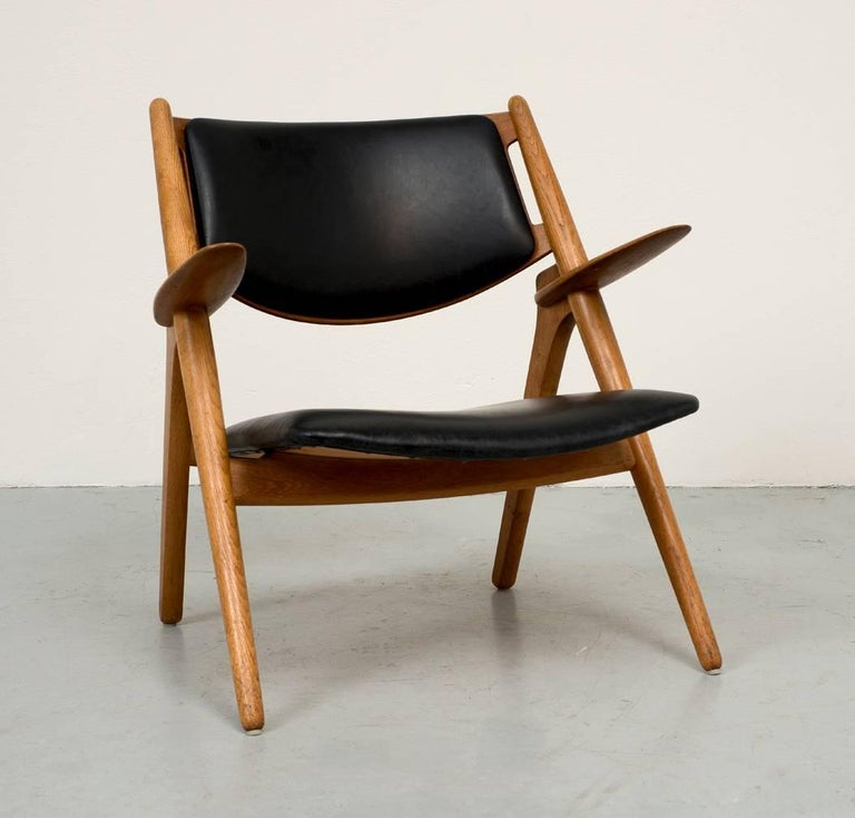 A fine example of Hans Wegner's CH-28 sawbuck lounge chair in oak and black leather. It is an iconic design that is at once sculptural, minimal and elegant. In excellent original condition.