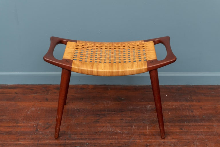 Hans Wegner design stool model JH539 made of sculpted teak with a cabe seat, labeled. In excellent original condition, with two small breaks that have since been repaired.