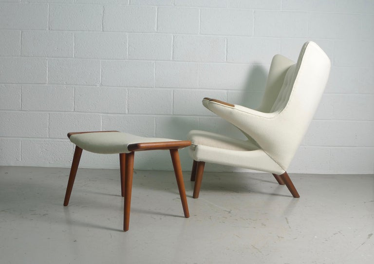 Hans Wegner for AP Stolen, Denmark, 1951. A model AP 19 Papa Bear and ottoman . An iconic chair beautifully reupholstered with white Kvadrat wool , contrasting seat cushion and ottoman . Chair has teak paws and legs , ottoman all teak .  Both