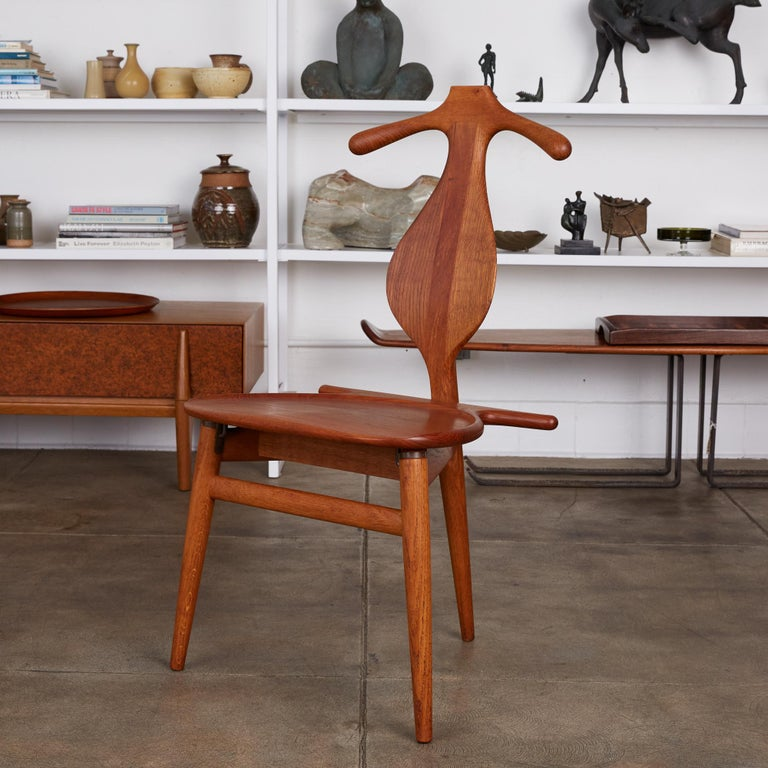 The iconic three legged valet chair designed by Hans J. Wegner for Johannes Hansen. The original four legged piece was conceived by Wegner after a discussion with his colleagues about issues with how to fold one's clothing at the end of the day. He