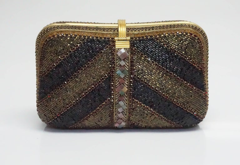 Hansen Designs Vintage Jeweled Clutch  This spectacular vintage piece is completely covered in jewels, beads, and stones. There is gold hardware throughout the clutch. Inside the clutch it is lined with fabric and has a side pocket. This bag can be