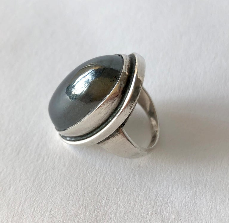 Hematite cabochon stone set in sterling silver ring designed by Harald Christian Nielsen for Georg Jensen, circa 1950.  Ring is a finger size 8.25 and is signed Georg Jensen, 46E, Denmark. In very good vintage condition.  Neilsen was a Danish
