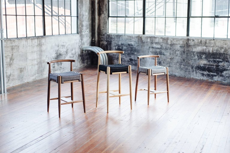 Phloem Studio Harbor stool is a modern contemporary solid walnut wood counter high stool handmade custom to order with turned tapered and shaped legs and tube backrest shaped from hardwood by hand. Available with a rope woven seat (shown here) or