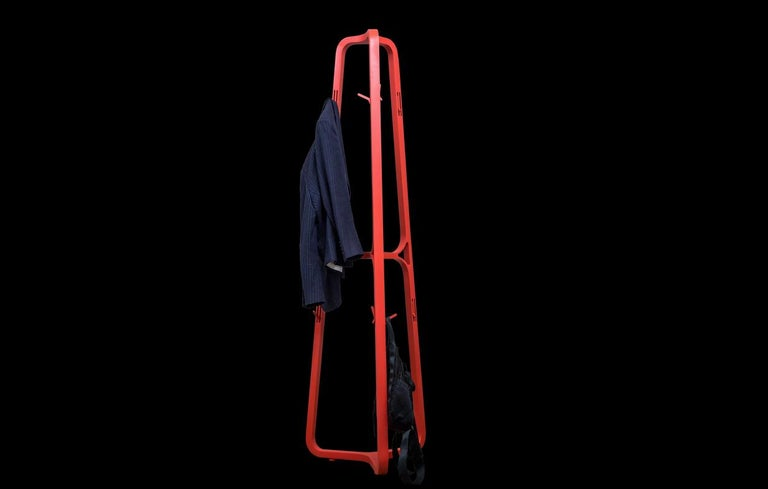 A playful coat rack made of Mexican wood finished with mate lacquer, features 12 holding hooks installed in a mechanism within the structure of the coatrack, that fold in and out to hang clothing and handbags.