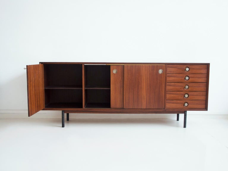 Long wooden sideboard manufactured by Faram in Italy, 1960s. Made of veneered hardwood, double sided sliding doors in white laminate and wood, legs in brushed steel tube with ferrules in solid wood. Metal handles.
