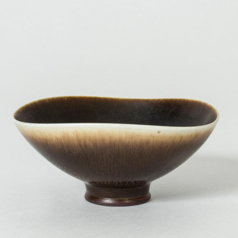 Lovely, small stoneware bowl by Berndt Friberg. Undulating rim, beautiful transition from brown hare's fur glaze to eggshell.