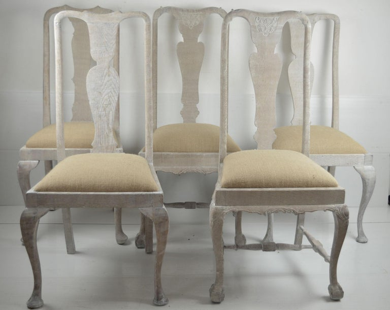 A set of 10 English limed oak chairs made up from 3 different near matching sets. ( 3 + 3 + 4 )  Each chair has the same basic characteristics: a delightful urn back splat, cabriole or Queen Anne legs and an elegantly understated top-rail. 3 of