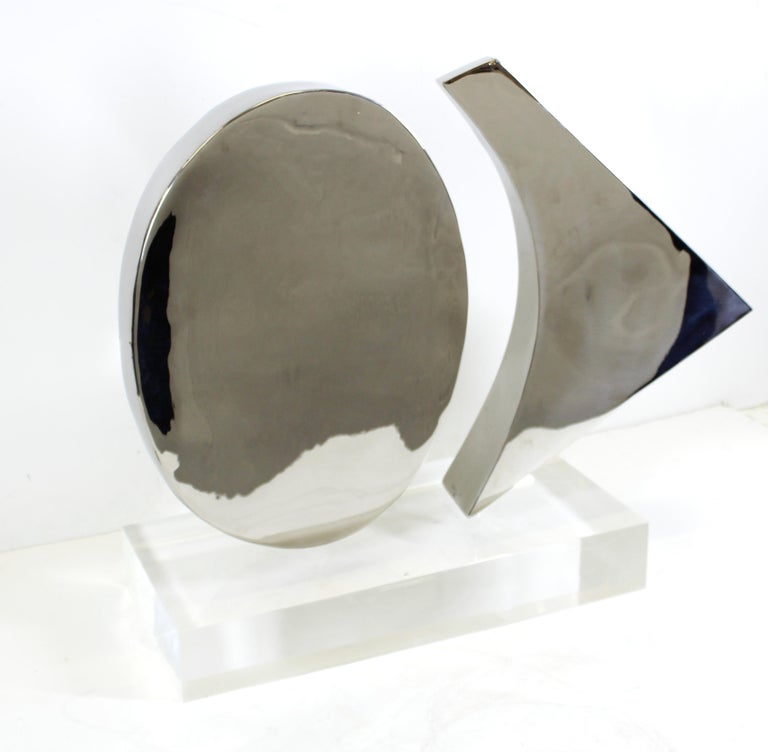 Modern abstract chromed metal sculpture of two rotating shapes mounted on a heavy acrylic base, created by New York artist Harold Sclar (NY 1930-2003), signed and dated 1977. In great vintage condition with age-appropriate wear and use.