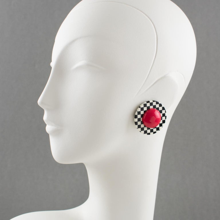Pretty Lucite clip-on earrings designed by Harriet Bauknight for Kaso. Dimensional rounded shape with a black and white checkerboard pattern and huge red half bead center. Kaso paper sticker missing but the specific rotating clip-fastenings are an