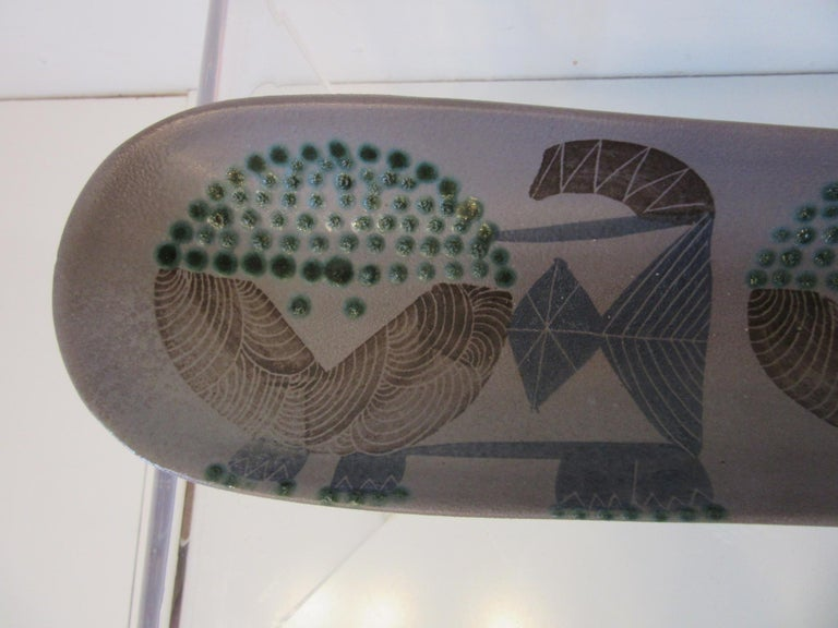 An early Harris G. Strong pottery fish tray or serving dish with glazed hand painted lions or animal forms to the surface. A rare piece signed to the bottom with style number P-30 and paper handwritten label.