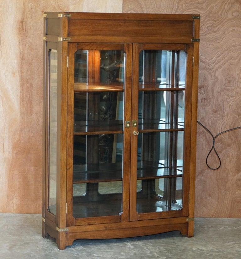 We are delighted to offer for sale this absolutely stunning Kennedy Furniture Military Campaign glass doored with mirror back and top light, display cabinet retailed through Harrods London   A very well made and utilitarian piece of furniture. It