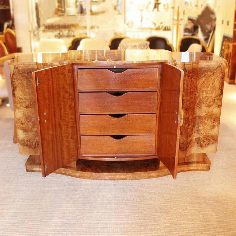 An Art Deco sideboard in burr walnut with original wooden handles. Central cabinet opens to a set of mahogany lined drawers. The right cabinet opens to a bottle turntable and the left side to mahogany lined shelves. Bow fronted with reeded detail.