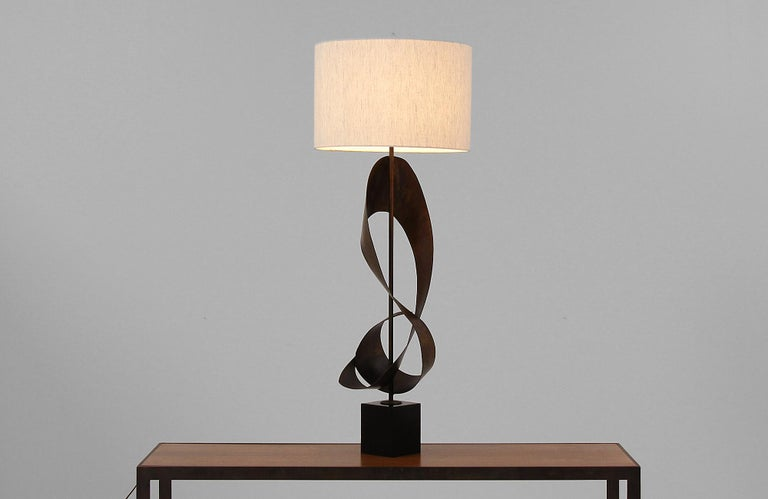 Brutalist ribbon-shaped table lamp designed in the United States by artist Harry Balmer for Laurel Lamp Co. circa 1960s. This stunning lamp features a modern abstract ribbon styled patinated steel body that sits on a black metal base for stability.