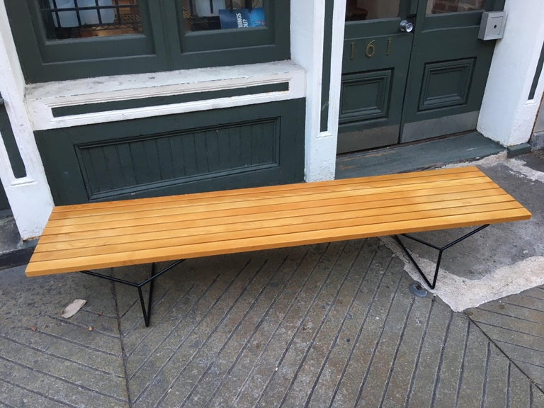Bertoia bench for Knoll. Longest version of the sizes offered. Solid oak slats with black iron legs. Retains original label. New finish. Measures: 82