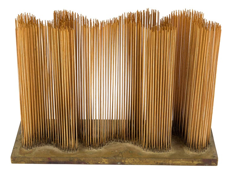 A sounding sculpture with straight vertical rods placed in an undulating wave pattern on a flat base. One of the rare small fine wire sonambients that produce a distinctive resonant sound.