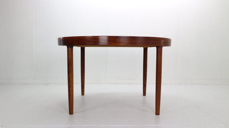 Exceptional dinning table designwed by Harry Østergaard for Randers Møbelfabrik manufacture in 1960s period, Denmark. The table is made of solid rosewood with beautiful wooden paternities over all.  Beautiful and unusual round leg joints and apron