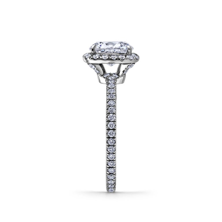 From the House of Harry Winston, this 1.28 carat cushion cut diamond platinum engagement ring symbolizes true love that will last a lifetime. Framed by pave-set round brilliant cut diamonds and a pave-set round brilliant cut diamond band weighing a