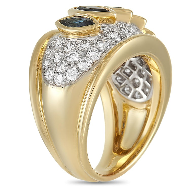 This Harry Winston ring features an opulent appearance that is virtually impossible to ignore. Its commanding presence begins with the 18K Yellow Gold band measuring 7mm wide. An array of glittering diamonds totaling 1.50 carats featuring E color