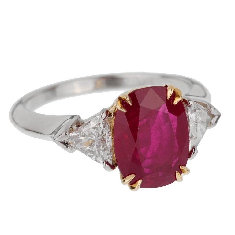 An iconic Harry Winston ring showcasing a 3.02ct Burma ruby set in 18k yellow gold flanked by 2 trillion cut diamonds in platinum. The ring measures a size 5 1/2 and can be resized.