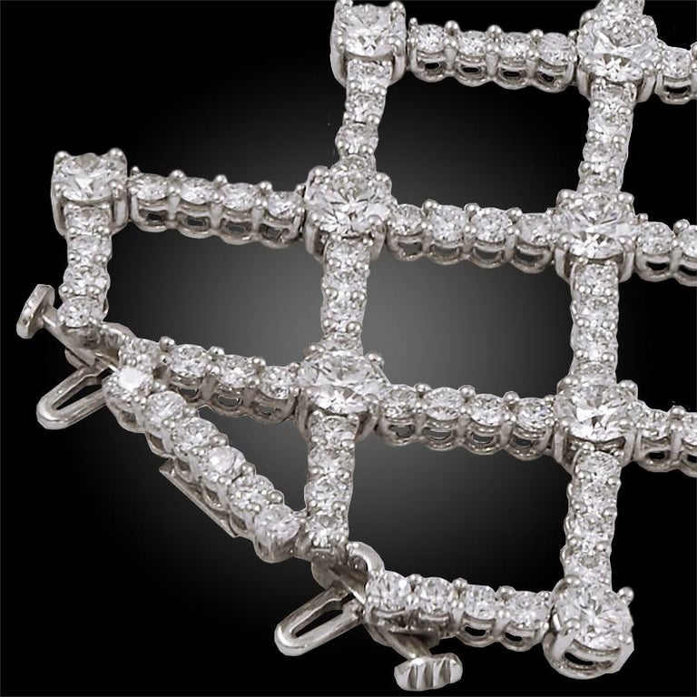 Comprising an exquisite platinum and diamond bracelet by Harry Winston, fashionably designed as several intersecting rows of round brilliant cut diamonds. The bracelet measures approximately 7 inches in length and 1.5 inches in width.   Signed Harry
