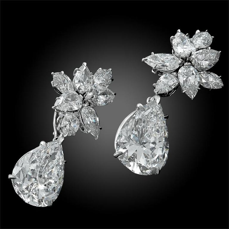 A remarkable set of 18k white gold cluster ear clips by Harry Winston dating back to the 1960s, comprised of 7 carats of brilliant diamonds set in a cluster design, and two hanging pear-shaped diamonds weighing  7.34 carats and 7.52 carats. The