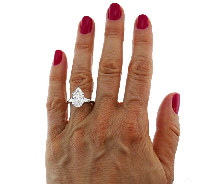 Timeless and elegant ring created by Harry Winston. Classic design, perfect proportions, the finest quality diamond! The ring is made of platinum and features a superb 3.60-carat pear brilliant cut diamond flanked by a pair of tapered baguette cut
