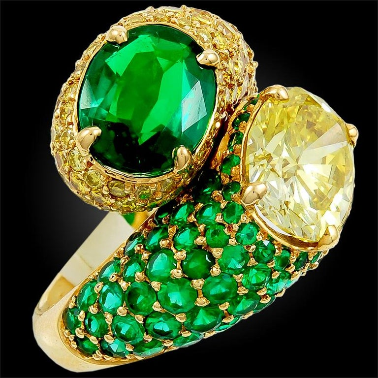 """A glorious ring by Harry Winston featuring a """"toi et moi"""" style set with a 2.54 carat fancy intense yellow diamond and a 1.94 carat Colombian emerald surrounded by the opulence of smaller brilliant cut fancy yellow diamonds and Colombian emeralds,"""