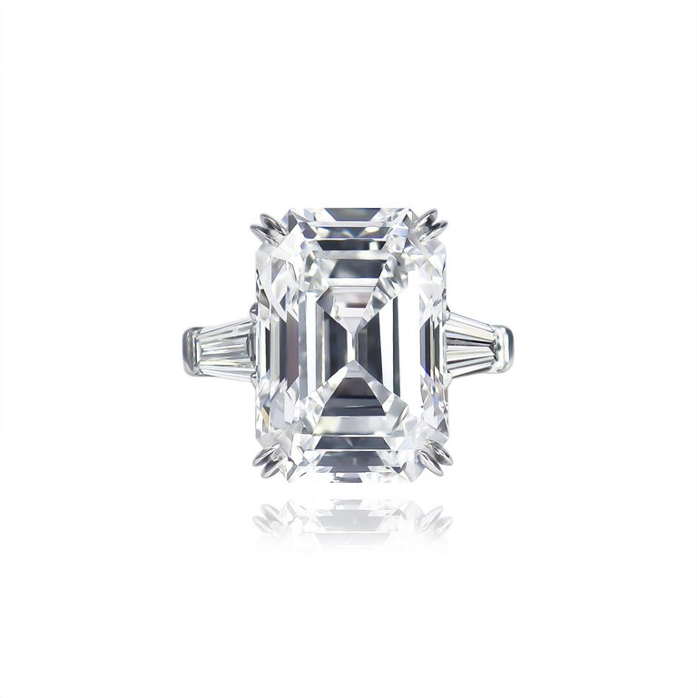 This exquisite ring from the house of Harry Winston features a 12.14 carat Emerald cut diamond of D color and Internally Flawless clarity as described by GIA grading report #5211073255. Set in a signed, platinum ring with tapered baguette side