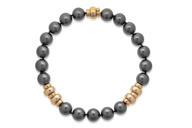 Exceptionally fine and rare Harry Winston hematite necklace with a gold clasp. It features hematite beads of 20mm in diameter. This necklace is further accented by a beautiful gold clasp figure.  HEMATITE AND GOLD EARRINGS, HARRY WINSTON; cabochons