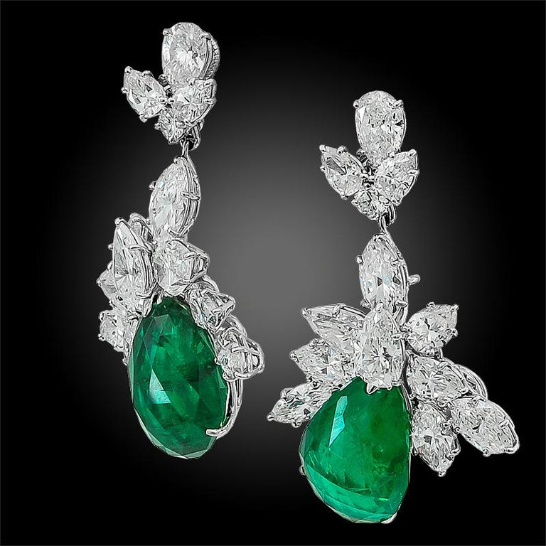 A luminous pair of dangling ear clips by Harry Winston circa 1960s,  set with 10.81 carats of pear shaped minor oil Colombian emeralds hanging from clusters of brilliant diamonds weighing approximately 9.70 carats. These earrings are detachable and
