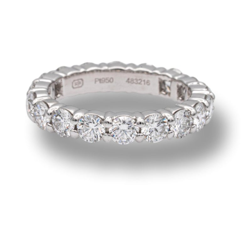 Harry Winston Diamond Eternity Anniversary band ring finely crafted in platinum with 18 round brilliant cut diamonds set in continuous shared prongs ranging D-F in color and VS2 and finer clarity. Comes in Harry Winston pouch and box.   Diamonds: