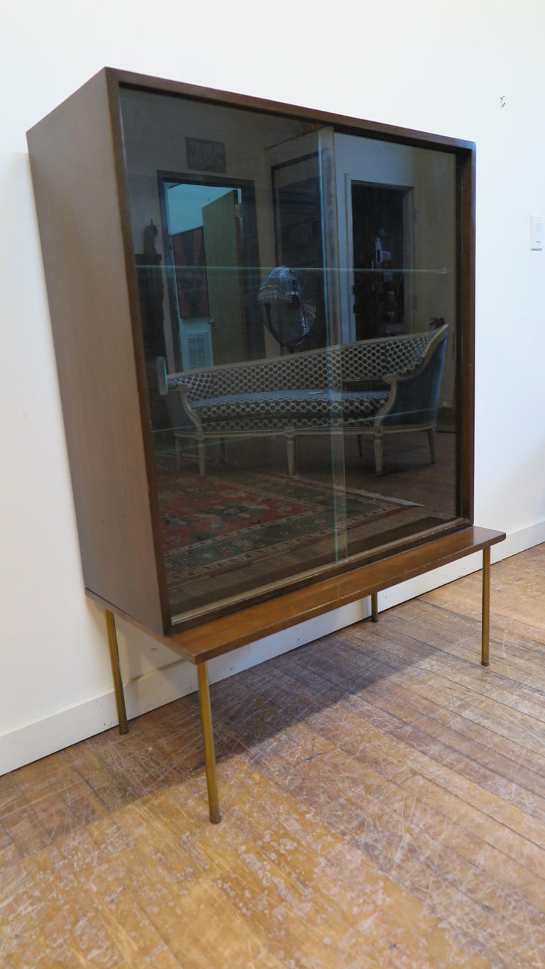 Harvey Probber cabinet with glass doors, two glass shelf's in a case set on stand with brass legs. This cabinet is in good original condition. Glass doors lift out easily if desired open face cabinet or display. Some fading, small dings, light