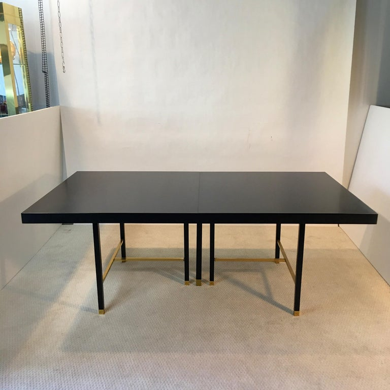 Magnificent minimalist design on a grand scale, ebonized mahogany dining table designed and produced by Harvey Probber, circa 1968 with solid brass square bar cross-stretchers and square leg sabots on seven legs, creating a striking profile both