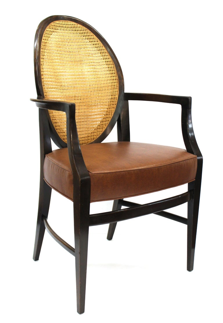 American Mid-Century Modern set of four armchairs with caned backs and faux-leather upholstered seats, attributed to Harvey Probber during the 1960s. The set is in great vintage condition and has been completely restored.