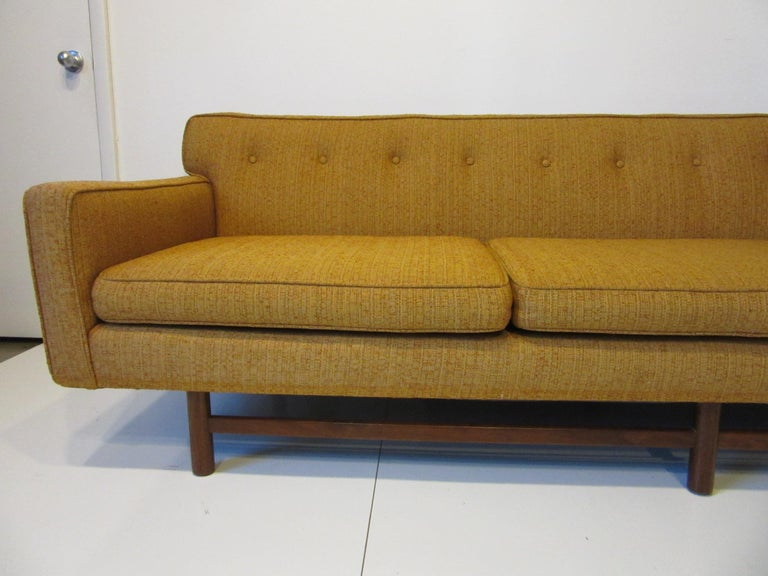 A three cushion low profile mid century sofa with button back and dark walnut legs and stretchers with overhang to each end that gives the sofa a floating affect. Designed in the manner of the Harvey Probber Furniture company, the sofa has great