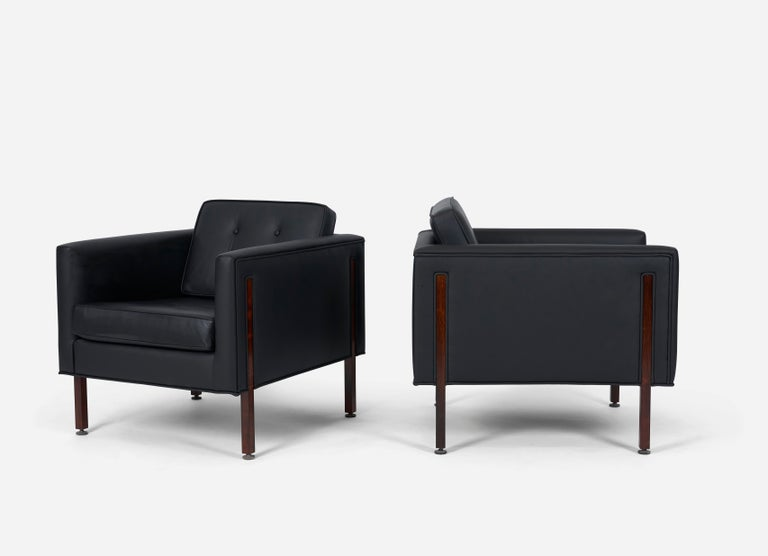Pair of club chairs in the style of Harvey Probber. Fully restored. New black leather upholstery with striking rosewood legs that run up the sides of chairs.