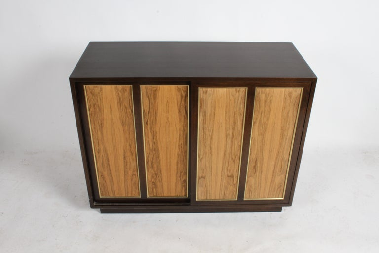 Harvey Probber Mid-Century modern bleached rosewood and mahogany dresser with brass trim. Sliding doors open to set of 8 drawers with white painted doors. Nice small or compact size dresser. Price includes refinishing of mahogany case and touch up