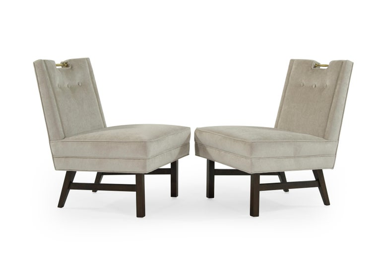 Rare pair of slipper chairs designed by Harvey Probber for Probber Inc., circa 1950s.  Newly upholstered in natural velvet, walnut bases fully restored. Solid brass handle atop the chair of easy movement.