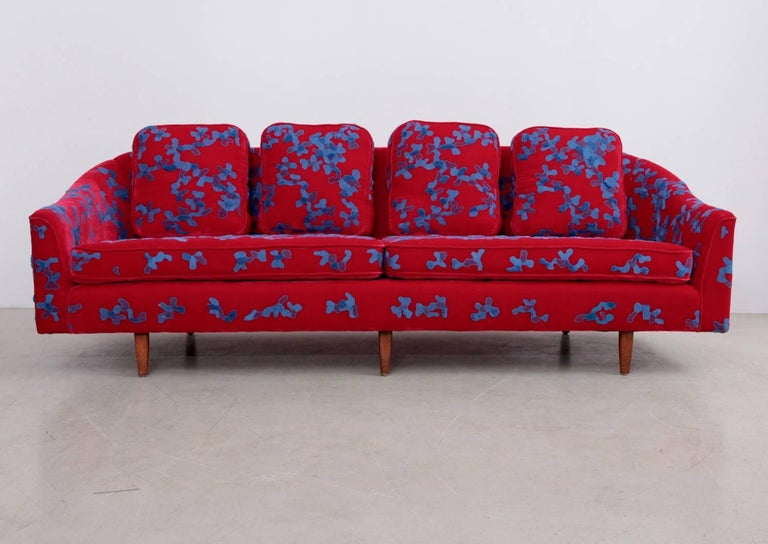 Hard to believe, that this art piece is completely hand embroidered by master artisans in India. The superb color combination of sky blue cotton thread on the deep red silk velvet base fabric give this eye-catching vintage Harvey Probber sofa dated