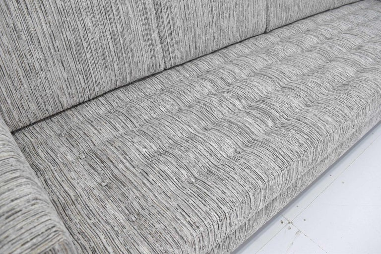 Newly upholstered in a chenille weave fabric that works with many color schemes. Beautiful lines. A Classic. Six walnut legs.