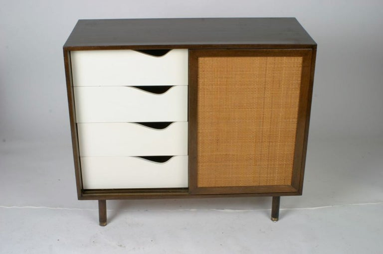 Harvey Probber two-door cabinet or dresser with sliding cane front doors, white painted drawers on one side, shelf on the other, brass sabots on legs. Label. Original finish restored. Note one shown is sold, new photos coming soon.