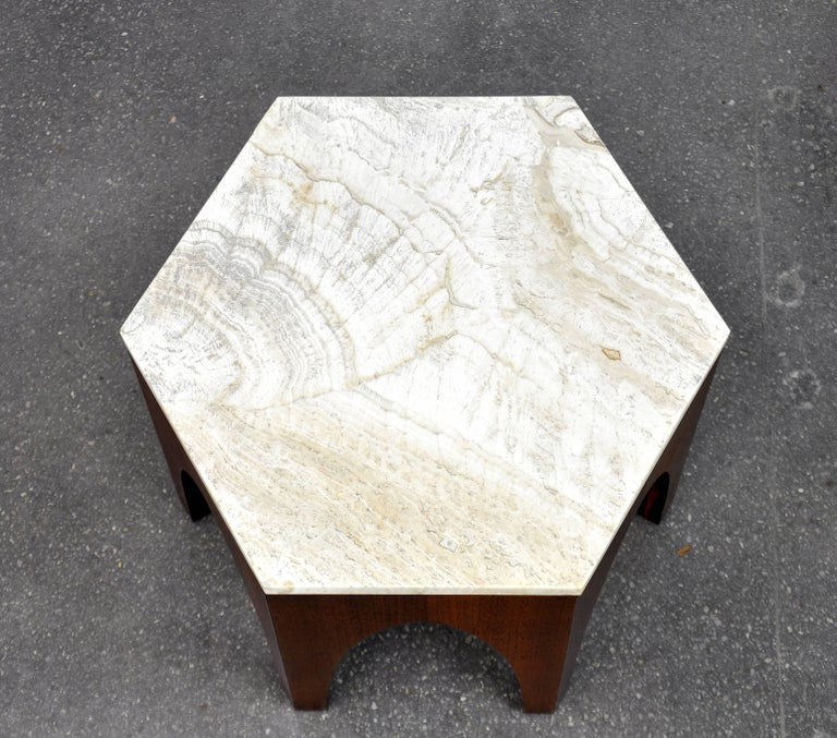 A great 1960s Mid-Century Modern end or occasional hexagon table designed by Harvey Probber. It features an Italian travertine inset top over a walnut base with Moroccan inspired arches. Being finished on all sides, it could also be used as a plant