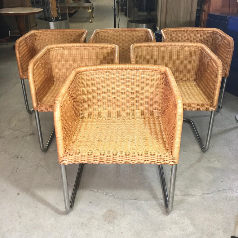 Hard to find a set of six of these comfortable and chic woven rattan and chromed tubular steel chairs from Harvey Probber. These are all in very good condition with no broken fibers and only slight wear to the varnish on top of the arms. They also