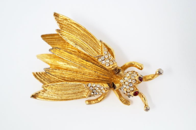 This whimsical insect trembler brooch, attributed to Hattie Carnegie circa 1940s, has wings on tiny springs so that they flutter with every movement.  Covered in gold-plating and crystal rhinestone pavé, this little bug is such a fun and unique
