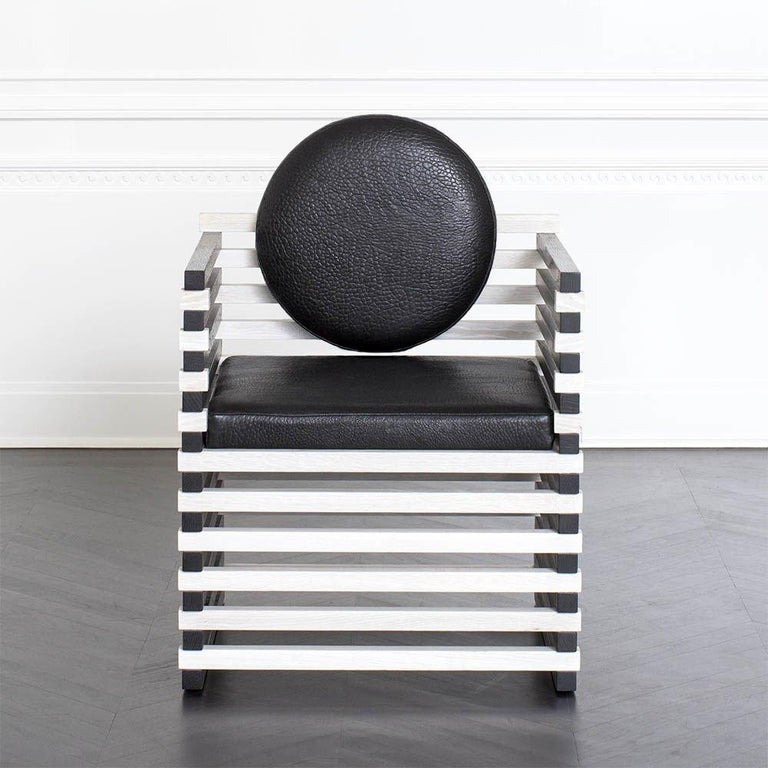 This graphic and elegant armchair is constructed from solid oak in alternating bleached and ebonized finishes. The circular back cushion heightens the sculptural allure of this occasional seating option. Perfect paired in an entryway or abutting a
