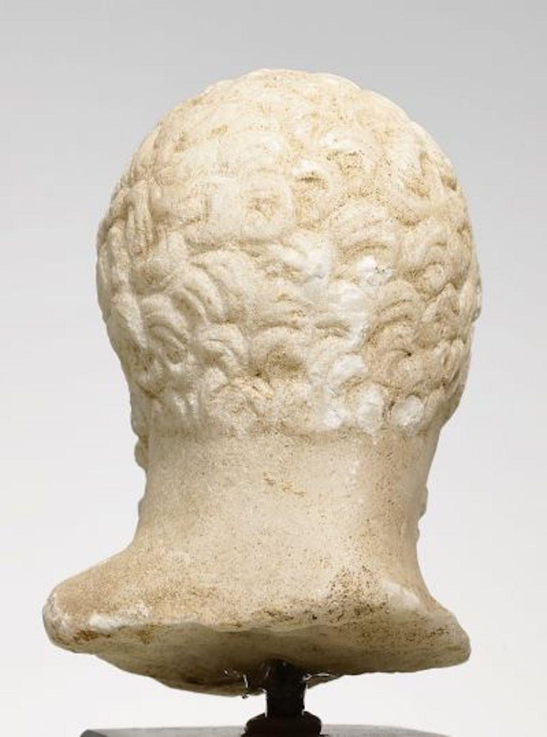 "Hellenistic, ca. 2nd/1st century BC Fine white crystalline marble. H. 6,5 cm.  A small head of a marble figurine of the ""Herakles Farnese"" type. The hero's head is slightly turned downwards, wearing a long wooly beard and short curly hair. A typical"