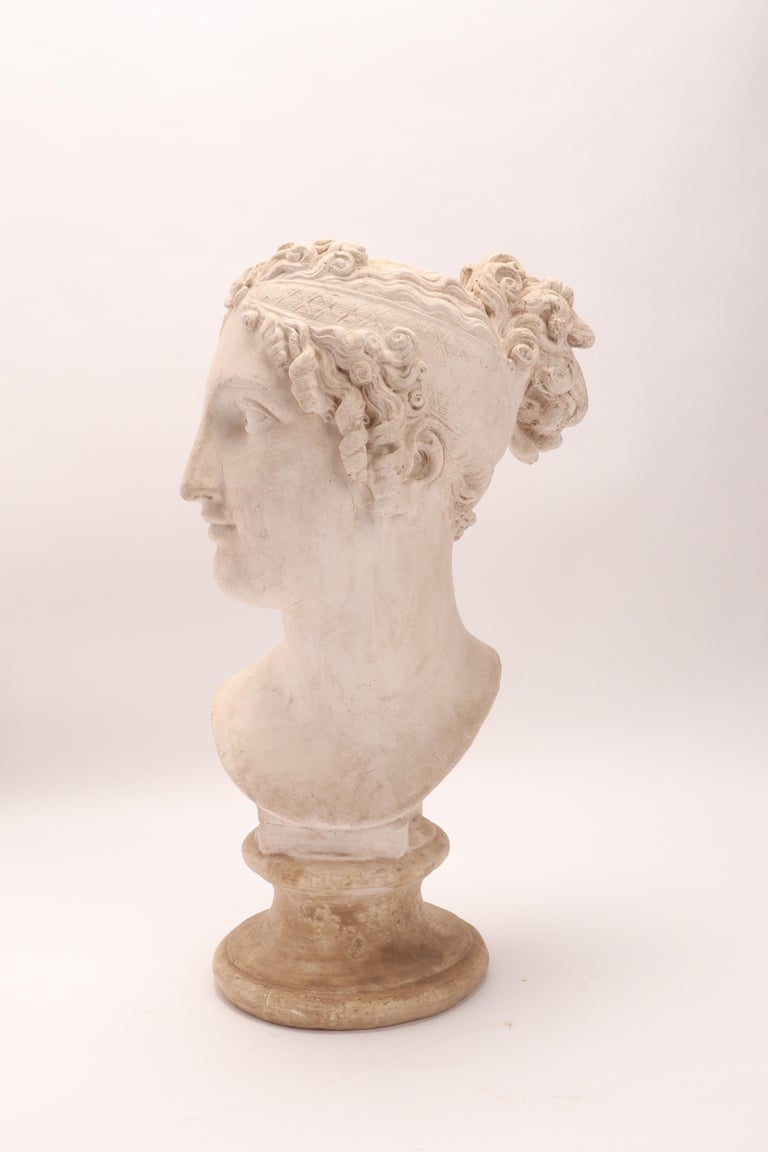 Above the plaster base, there is a plaster cast of a woman's head, a neoclassical portrait. A cast for the teaching drawing in the academy, Italy, circa 1890.
