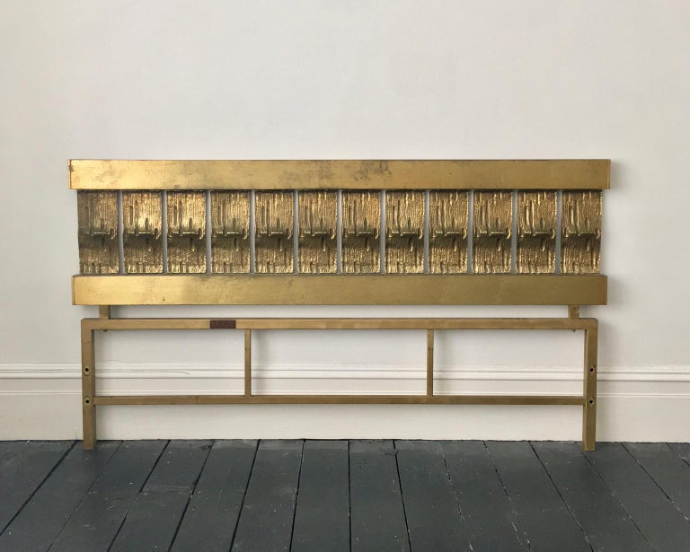 A mid-century modern headboard of cast and hammered brass, by Luciano Frigerio, Italy.  This is a statement piece, with a simple block-like construction, which gives it a strong Brutalist feel. The upper section comprises two cross-bars with